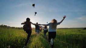 De gelukkige hogere leerlingen vluchten en werpen hun portefeuilles tegen de zonsondergang Gelukkige beëindigende schooldagen Lan stock afbeelding