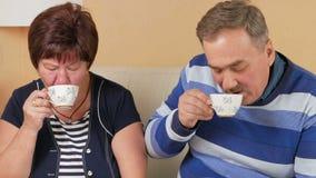De gelukkige hogere mens brengt een kop van uw favoriete koffie Drink een hete drank en bespreek een grote familiegebeurtenis Moo stock video