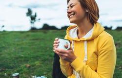 De gelukkige holding van het glimlachmeisje in handenkop van hete thee op groen gras in in openlucht aardpark, mooie jonge vrouw  stock foto's