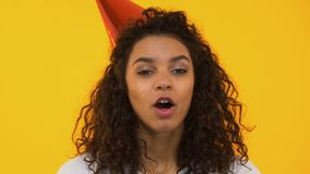 De gelukkige hoorn van de meisjes blazende die partij, het vieren Verjaardag, op achtergrond wordt geïsoleerd stock videobeelden