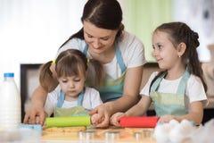 De gelukkige houdende van familiemoeder en haar dochters bereiden samen bakkerij voor Het mamma en de jonge geitjes koken koekjes stock afbeeldingen