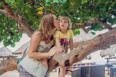 De gelukkige houdende van jonge moeder kust haar peuterzoon op de gang Stock Afbeelding