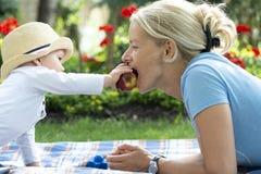 De gelukkige houdende van moeder en haar baby eten een appel royalty-vrije stock afbeeldingen