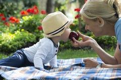 De gelukkige houdende van moeder en haar baby eten een appel royalty-vrije stock foto's