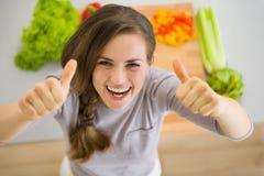 De gelukkige huisvrouw in keuken het tonen beduimelt omhoog Stock Afbeelding