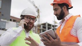 De gelukkige ingenieur spreekt op Mobiele telefoon op bouwwerf en controleert het werk van de arbeider Bouwersbesprekingen  stock video