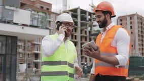 De gelukkige ingenieur spreekt op Mobiele telefoon op bouwwerf en controleert het werk van de arbeider Bouwersbesprekingen  stock videobeelden