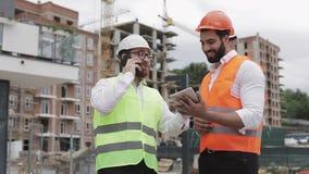 De gelukkige ingenieur spreekt op Mobiele telefoon op bouwwerf en controleert het werk van de arbeider Bouwersbesprekingen  stock footage