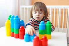 De gelukkige 2 jaar peuter speelt plastic blokken Stock Foto's