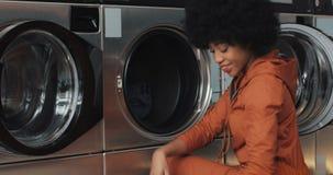 De gelukkige jonge Afrikaanse Amerikaanse vrouw zit voor een wasmachine en laadt de wasmachine met vuile wasserij zelf stock video