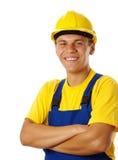 De gelukkige jonge arbeider vouwt zijn wapens en glimlach Stock Afbeeldingen