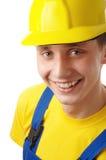 De gelukkige jonge arbeider vouwt zijn wapens en glimlach Stock Foto