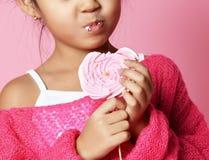 De gelukkige jonge Aziatische lik van het meisjejonge geitje eet gelukkig groot zoet lollypopsuikergoed op roze royalty-vrije stock afbeelding