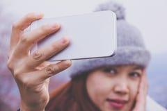 De gelukkige jonge Aziatische vrouwen bekijken haar cellphone Royalty-vrije Stock Foto's