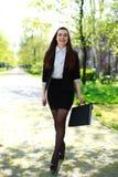 De gelukkige jonge bedrijfsvrouw loopt in stadspark Royalty-vrije Stock Fotografie