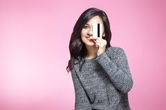 De gelukkige jonge die creditcard van de vrouwenholding over roze achtergrond wordt geïsoleerd stock foto's