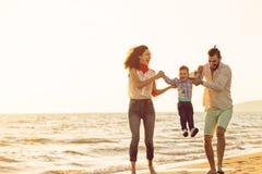 De gelukkige jonge die familie heeft pret op strand en sprong bij zonsondergang in werking wordt gesteld stock foto