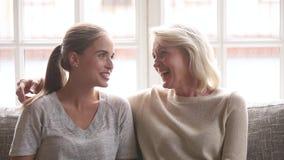 De gelukkige jonge dochter en de hogere moeder die pret hebben genieten van bespreking stock video
