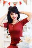 De gelukkige jonge donkerbruine vrouw in rode kleding is in Kerstmis verfraait Royalty-vrije Stock Afbeeldingen