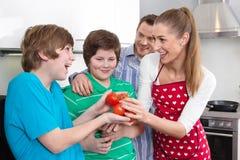 De gelukkige jonge familie heeft pret in de keuken - samen kokend Stock Afbeeldingen