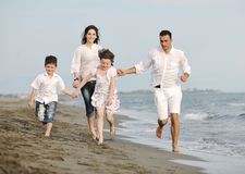 De gelukkige jonge familie heeft pret op strand Stock Afbeeldingen