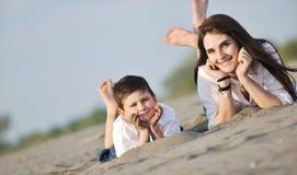 De gelukkige jonge familie heeft pret op strand royalty-vrije stock foto's