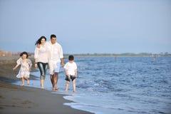 De gelukkige jonge familie heeft pret op strand stock foto's