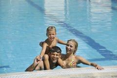 De gelukkige jonge familie heeft pret op zwembad Stock Afbeeldingen