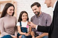 De gelukkige jonge familie krijgt sleutels aan nieuw huis, dat de makelaar in onroerend goed hielp om te kiezen De familie koopt  royalty-vrije stock afbeelding