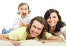 De gelukkige jonge familie ligt op pluizig bont stock afbeelding