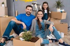 De gelukkige jonge familie ontmantelt kartondozen en maakt reparaties in nieuw huis stock afbeeldingen