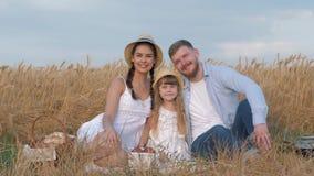 De gelukkige jonge familie, vrolijke ouders met weinig kindmeisje koestert en bekijkt en elkaar die uitje glimlachen aanwezig zij stock video