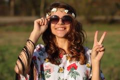 De gelukkige jonge glimlachen van de meisjeshippie en in openlucht het tonen van teken van vrede Royalty-vrije Stock Foto