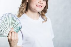 De gelukkige jonge glimlachende vrouw houdt ons dollargeld in hand over witte achtergrond stock afbeelding
