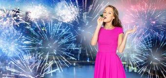 De gelukkige jonge hoorn van de vrouwenpartij over vuurwerk bij stad Royalty-vrije Stock Foto