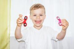 De gelukkige jonge jongen die twee houden friemelt spinners Royalty-vrije Stock Foto's