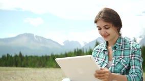 De gelukkige jonge Kaukasische donkerbruine vrouw met tablet in park op de zonnige zitting van de de zomerdag op gras, rug stak,  stock footage