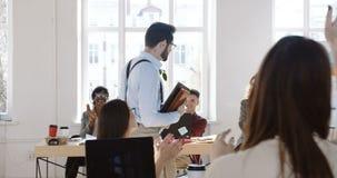 De gelukkige jonge Kaukasische zakenmangangen langs modern licht multi-etnisch bureau, collega's wensen hem geluk die slaan stock video