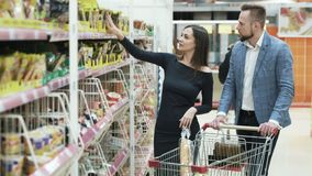 De gelukkige jonge man en de vrouw kiezen producten in supermarkt stock videobeelden