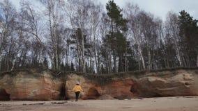 De gelukkige jonge manier wijdde vrouw die sporten op het strand in koud de Lenteweer doen - Veczemju Klintis, Letland - April stock footage