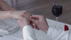 De gelukkige jonge mens die een voorstel doen die verlovingsring geven aan zijn fiancee in een restaurant, sluit omhoog handen Royalty-vrije Stock Afbeeldingen
