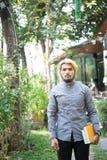 De gelukkige jonge mens die en notitieboekjes bevinden zich houden tuiniert thuis e stock foto