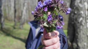 De gelukkige jonge mens geeft het meisje een boeket van wilde bloemen De lentepark, romantische datum stock footage