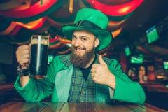 De gelukkige jonge mens zit bij lijst in bar en stelt op camera Hij houdt mok donker bier De kerel kijkt gelukkig Hij draagt St P stock afbeelding