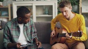 De gelukkige jonge mensen Kaukasische en Afrikaanse Amerikaan hebben pret die thuis de gitaar spelen en tablet gebruiken genieten stock footage
