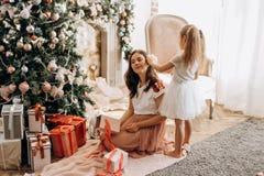 De gelukkige jonge moeder en haar weinig dochter in aardige kleding zitten Ne stock afbeelding
