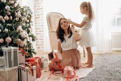 De gelukkige jonge moeder en haar weinig dochter in aardige kleding zitten Ne royalty-vrije stock afbeeldingen