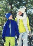 De gelukkige jonge moeder en het kind gekleed in heldere sportkleding hebben samen pret tegen Kerstmisboom Royalty-vrije Stock Afbeeldingen