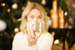 De gelukkige jonge mooie vrouw het glimlachen doos van de holdings kleine gift Vrolijke vrouw met een gift in haar handen stock foto