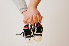 De gelukkige jonge ouders houden in hun handen kinderen` s schoenen van futu Royalty-vrije Stock Fotografie
